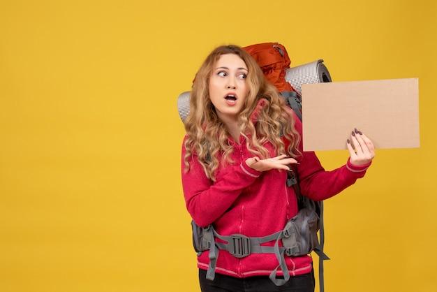 Jovem chocada e viajando recolhendo sua bagagem e mostrando espaço livre para escrever