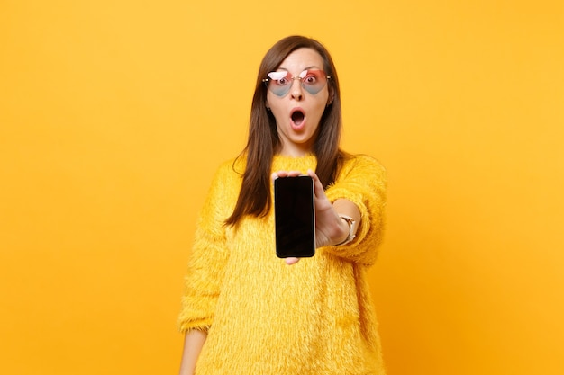 Jovem chocada em copos de coração, mostrando na câmera do telefone móvel com tela vazia preta em branco isolada em fundo amarelo brilhante. emoções sinceras de pessoas, conceito de estilo de vida. área de publicidade.