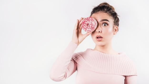 Jovem chocada fazer beicinho seus lábios cobrindo os olhos com donut em pano de fundo branco