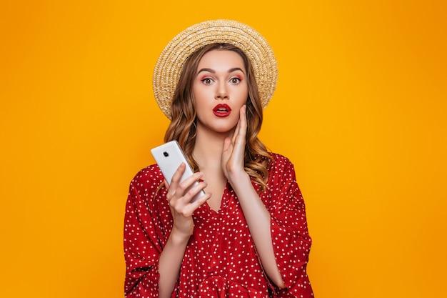 Jovem chocada no chapéu de palha vestido vermelho com batom vermelho em pé com smartphone e olhando para a câmera isolada em uma parede laranja. garota surpresa com um telefone móvel em roupas de verão