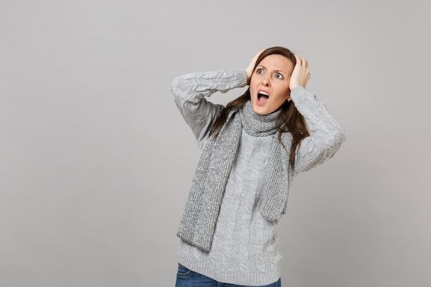 Jovem chocada num suéter cinza, lenço olhando para cima, colocando as mãos na cabeça, gritando isolado em um fundo cinza. estilo de vida de moda saudável, conceito de estação fria de emoções de pessoas. simule o espaço da cópia.