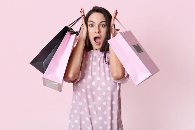 Jovem chocada segurando sacolas de compras
