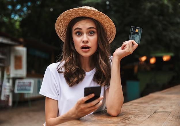 Jovem chocada segurando um cartão de crédito de plástico enquanto usa o telefone celular em um café ao ar livre