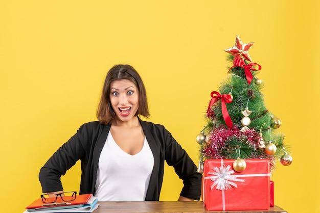 Jovem chocada sentada à mesa em um terno perto da árvore de natal decorada no escritório em amarelo