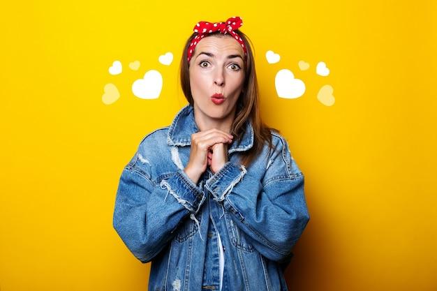 Jovem chocada surpresa com faixa de cabelo, em uma jaqueta jeans em uma parede amarela.