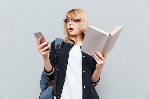Jovem chocada usando telefone e segurando o livro.