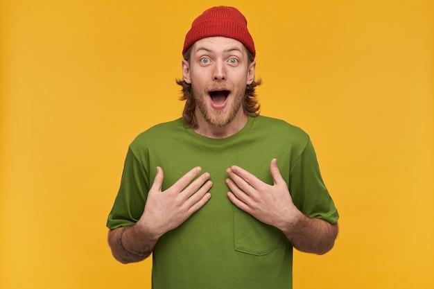 Jovem, chocado cara com cabelos loiros, barba e bigode. vestindo camiseta verde e gorro vermelho. tem tatuagem. apontando para si mesmo. não posso acreditar. isolado sobre a parede amarela