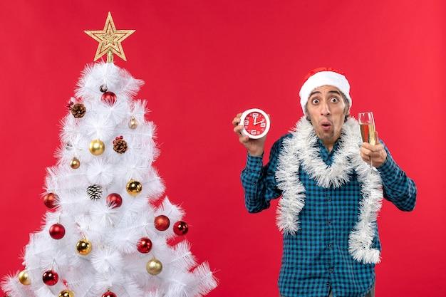 Jovem chocado com chapéu de papai noel, segurando uma taça de vinho e um relógio em pé perto da árvore de natal