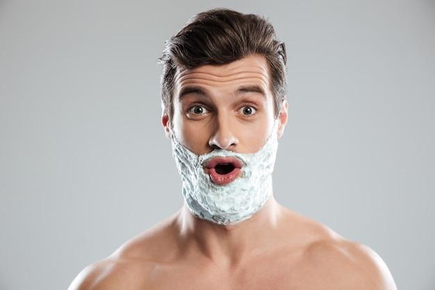 Jovem chocado com espuma de barbear no rosto