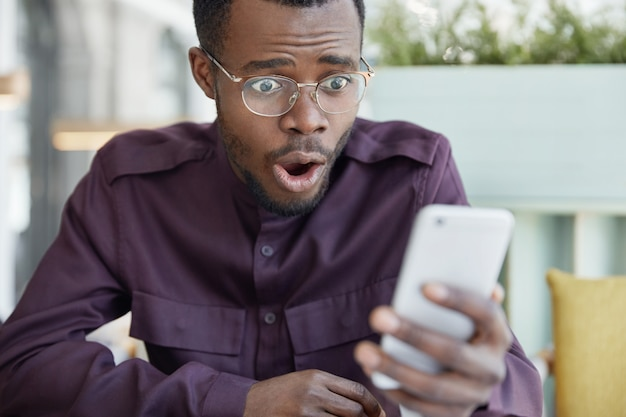 Jovem chocado, de pele escura e óculos, surpreso ao receber o recibo da conta no celular, estressado por ler notícias chocantes