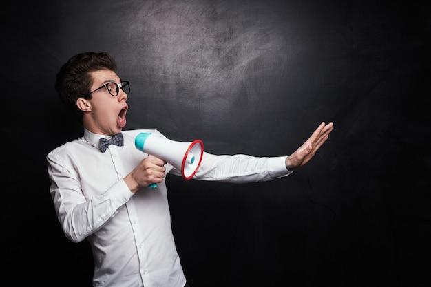 Jovem chocado e animado em uma camisa branca formal com gravata borboleta e óculos de nerd esticando o braço e gritando alto com um megafone contra um fundo preto
