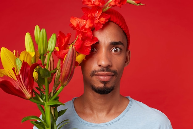 Jovem chocado e atraente com chapéu vermelho e camiseta azul, segura um buquê nas mãos e parte do rosto coberta com flores, olha para a câmera com os olhos bem abertos, fica sobre o backgroud vermelho.
