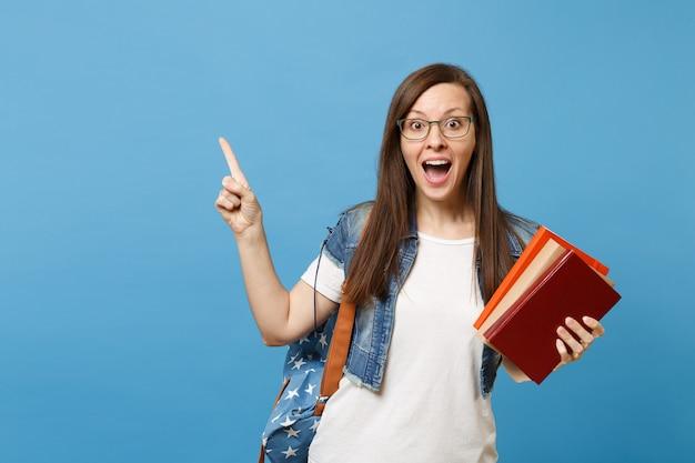 Jovem chocado e espantado estudante mulher com a boca aberta em copos com mochila apontando o dedo indicador para cima, segurando livros escolares isolados sobre fundo azul. educação na faculdade universitária do ensino médio.