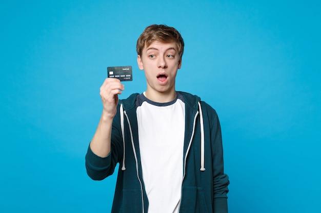 Jovem chocado em roupas casuais segurando, olhando no cartão do banco de crédito, mantendo a boca aberta isolada na parede azul. emoções sinceras de pessoas, conceito de estilo de vida.