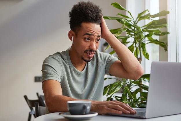 Jovem chocado rapaz atraente de pele escura, senta-se em um café e trabalha em um laptop, olha para o monitor com expressão de surpresa, lê o artigo com notícias atordoadas.