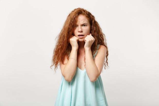 Jovem chocado ruiva preocupada garota mulher em roupas leves casuais posando isolado no fundo branco no estúdio. conceito de estilo de vida de emoções sinceras de pessoas. simule o espaço da cópia. coloque o apoio da mão no queixo.