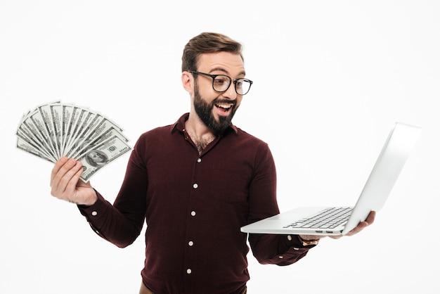 Jovem chocado segurando dinheiro e computador portátil.