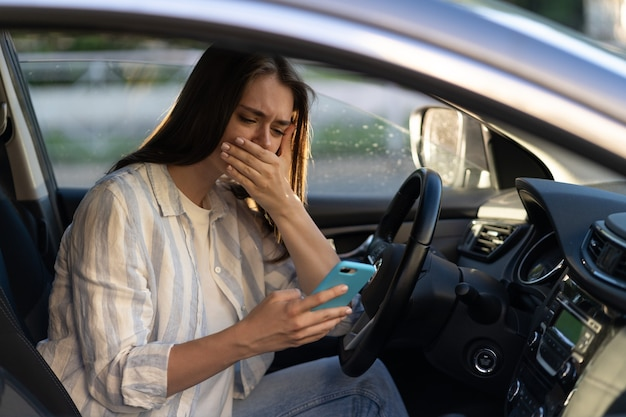 Jovem chorando lendo mensagem no telefone celular jovem frustrada e chateada no banco do motorista do carro
