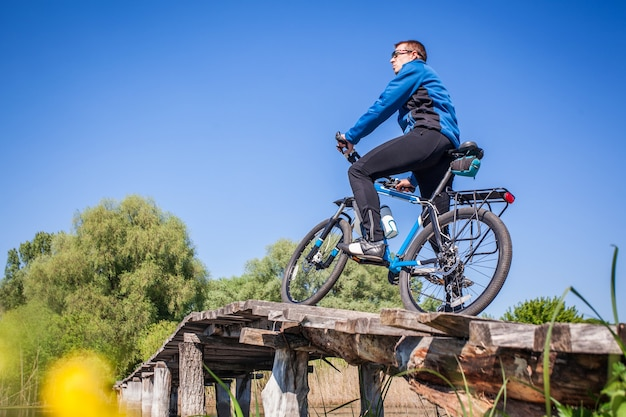 Jovem ciclista andando de mountain bike na ponte sobre o rio
