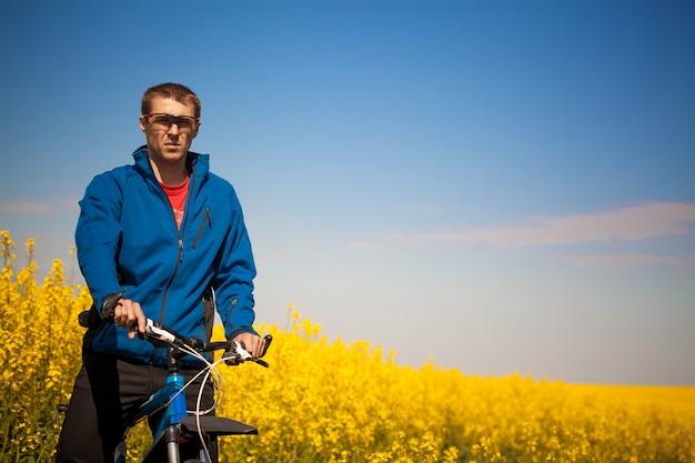 Jovem ciclista andando em campo de colza na primavera em mountain bike