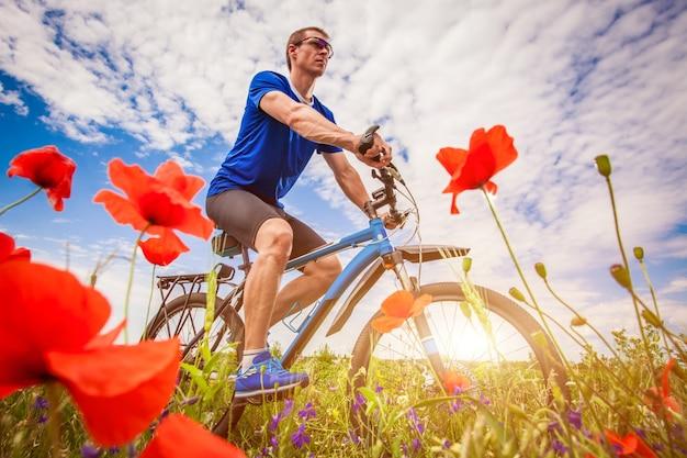 Jovem ciclista andando em campo de papoulas ao pôr do sol