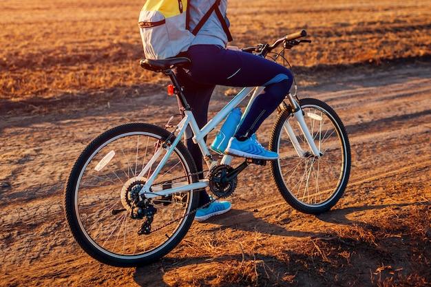 Jovem ciclista andando no campo de outono ao pôr do sol, mulher com mochila de viagem,