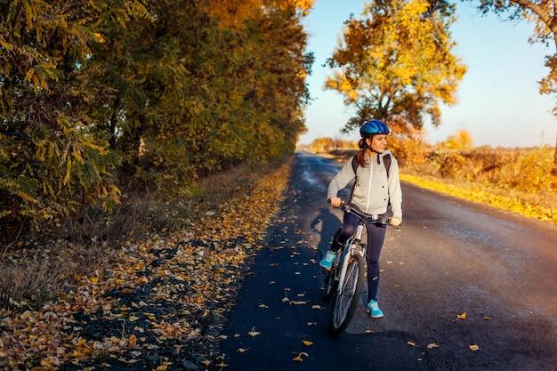 Jovem ciclista andando no campo de outono ao pôr do sol. mulher feliz sorrindo. modo de vida ativo