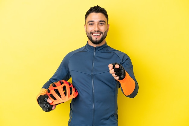 Jovem ciclista árabe isolado em um fundo amarelo surpreso e apontando para a frente