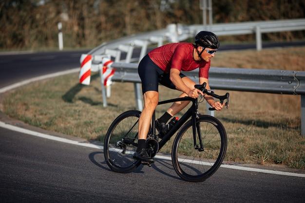Jovem ciclista ativo em roupas esportivas e capacete protetor, correndo em estrada asfaltada durante um dia ensolarado