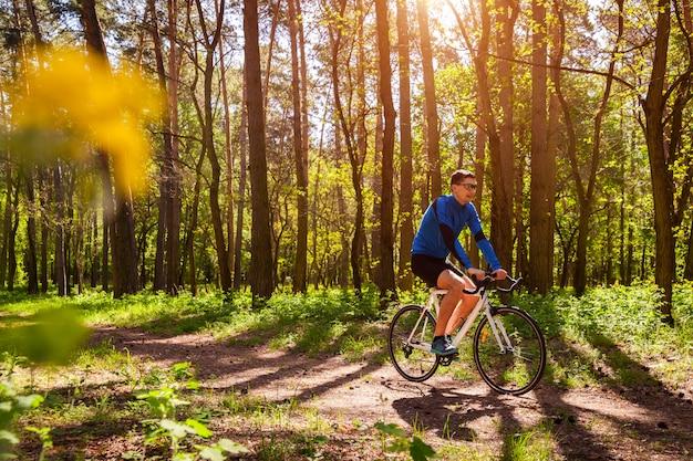 Jovem ciclista bicicleta na floresta de primavera