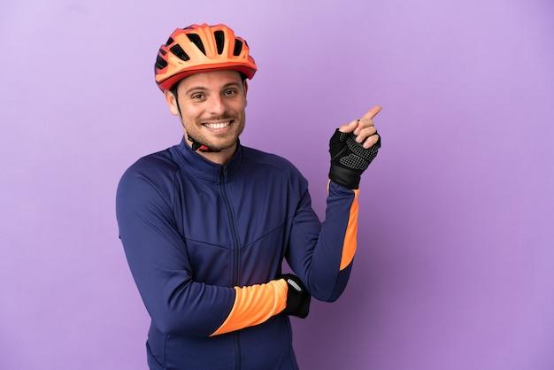 Jovem ciclista brasileiro isolado em fundo roxo apontando o dedo para o lado