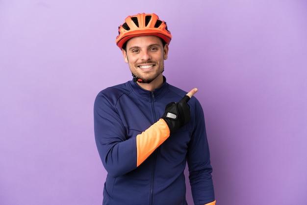 Jovem ciclista brasileiro isolado em fundo roxo apontando para o lado para apresentar um produto