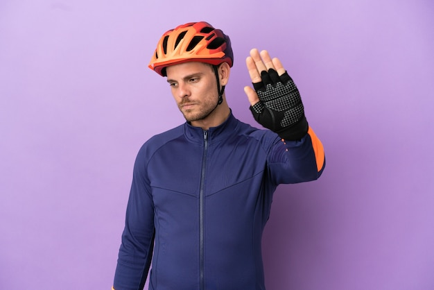 Jovem ciclista brasileiro isolado em fundo roxo fazendo gesto de pare e desapontado