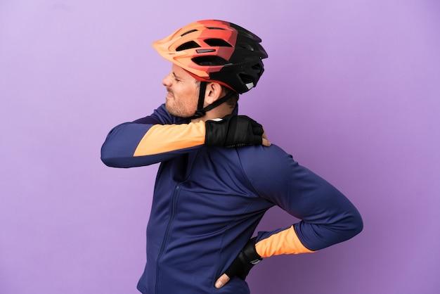 Jovem ciclista brasileiro isolado em fundo roxo sofrendo de dores no ombro por ter feito esforço