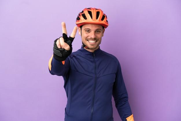 Jovem ciclista brasileiro isolado em fundo roxo sorrindo e mostrando sinal de vitória
