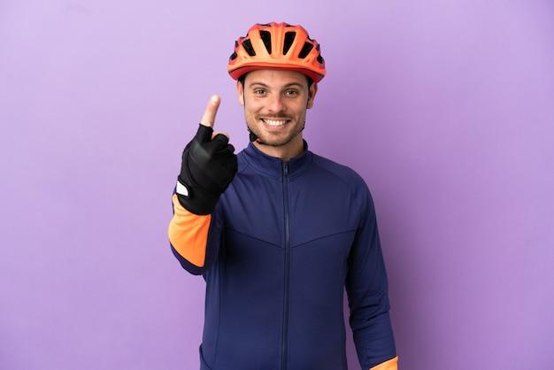 Jovem ciclista brasileiro isolado em um fundo roxo fazendo gesto de aproximação
