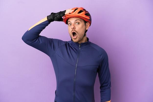 Jovem ciclista brasileiro isolado em um fundo roxo fazendo gesto surpresa enquanto olha para o lado