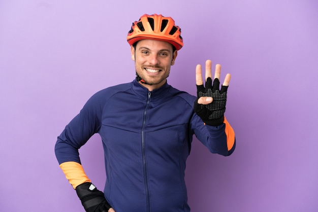 Jovem ciclista brasileiro isolado em um fundo roxo feliz e contando quatro com os dedos