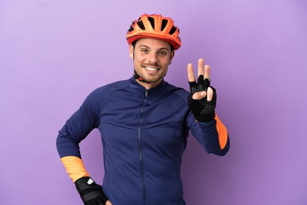 Jovem ciclista brasileiro isolado em um fundo roxo feliz e contando três com os dedos