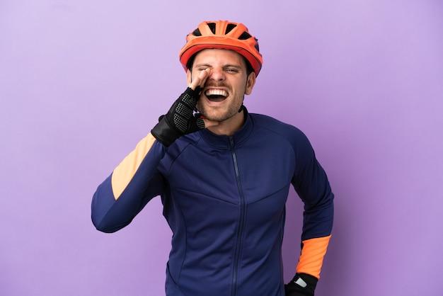 Jovem ciclista brasileiro isolado em um fundo roxo gritando com a boca bem aberta