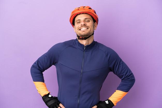 Jovem ciclista brasileiro isolado em um fundo roxo posando com os braços na cintura e sorrindo