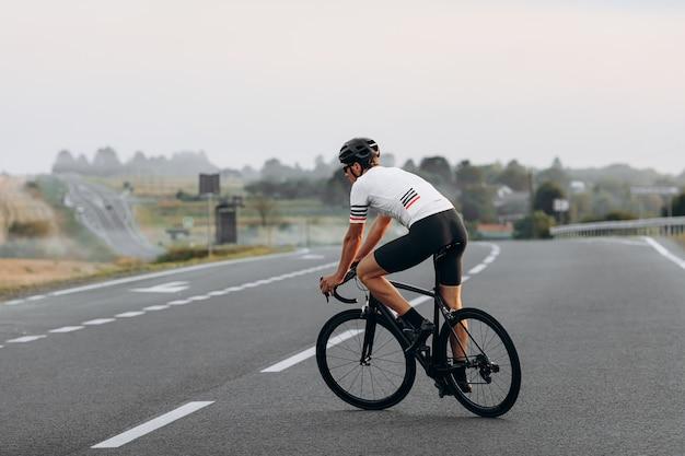 Jovem ciclista com corpo atlético vestido com roupas esportivas, correndo na estrada durante o dia de verão