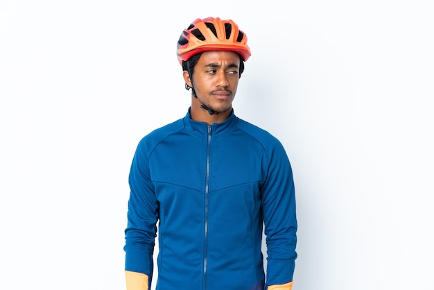 Jovem ciclista com tranças sobre fundo isolado, tendo dúvidas enquanto olha de lado