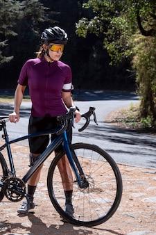 Jovem ciclista descansando com sua bicicleta na beira da estrada usando capacete e óculos escuros