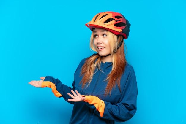 Jovem ciclista isolada em um fundo azul com expressão de surpresa enquanto olha para o lado