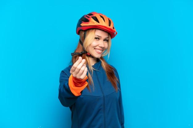 Jovem ciclista isolada em um fundo azul fazendo gesto de dinheiro