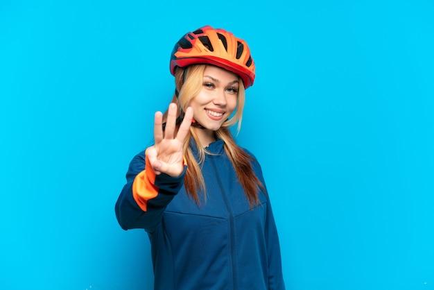 Jovem ciclista isolada em um fundo azul feliz e contando três com os dedos