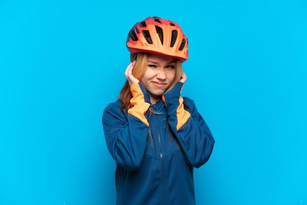 Jovem ciclista isolada em um fundo azul frustrada e cobrindo as orelhas