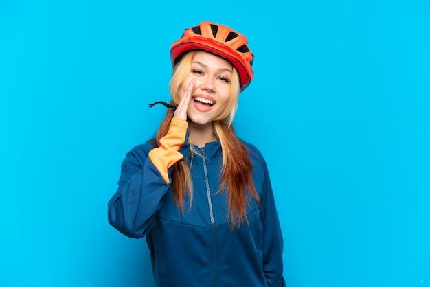 Jovem ciclista isolada em um fundo azul gritando com a boca bem aberta
