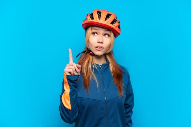 Jovem ciclista isolada em um fundo azul pensando em uma ideia apontando o dedo para cima